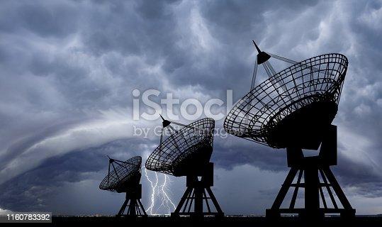 Three Communication Satellite dishes at thundershtorm .
