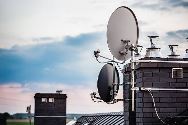 Satellite dishes, satellite antennas mounted on the chimney Satellite dishes, satellite antennas mounted on the chimney of a new home. Evening antenna aerial stock pictures, royalty-free photos & images