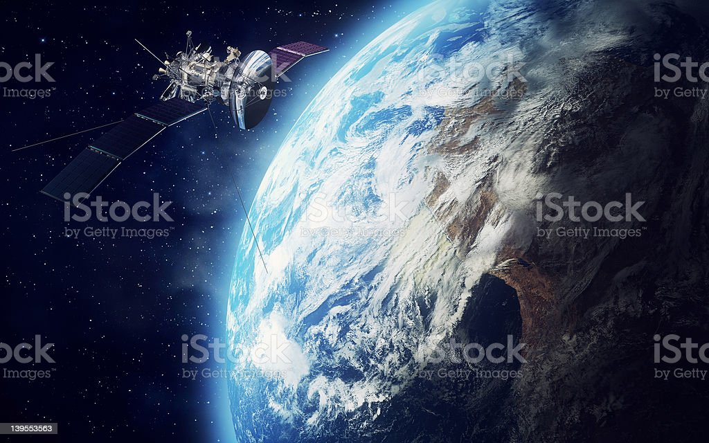 Satellite orbiting the earth in outer space stock photo