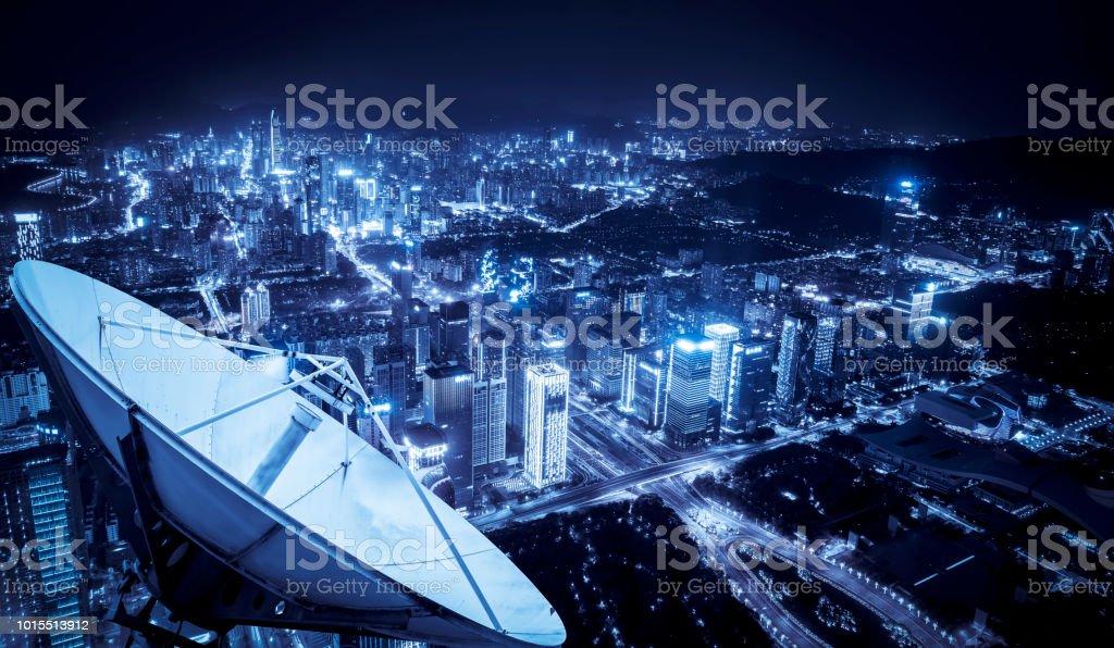 Receptor de señal de satélite sobre la ciudad - Foto de stock de Alto - Descripción física libre de derechos