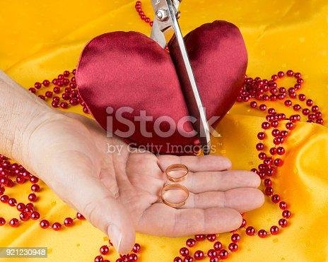 921231258istockphoto Satin heart cut with scissors. Broken heart. Divorce concept. Couple separation 921230948