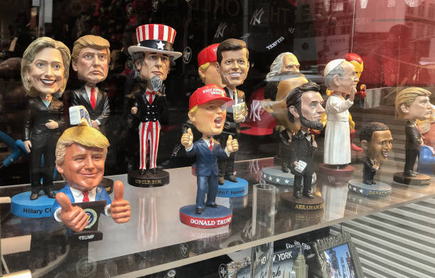 satirical dolls of political figures at a souvenir shop window display - trump стоковые фото и изображения