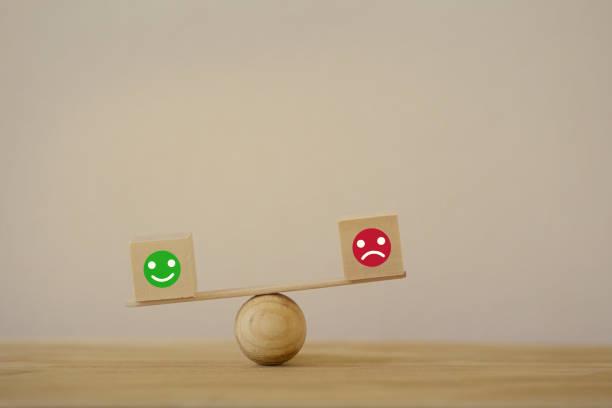 zufriedenheit skalenkonzept: symbol-symbol-smiley-gesicht und ein trauriges gesicht auf holzblockwürfel eine balance-skala in unalike. zeigt die besten exzellenten business services bewertung kundenerfahrung - feedback stock-fotos und bilder