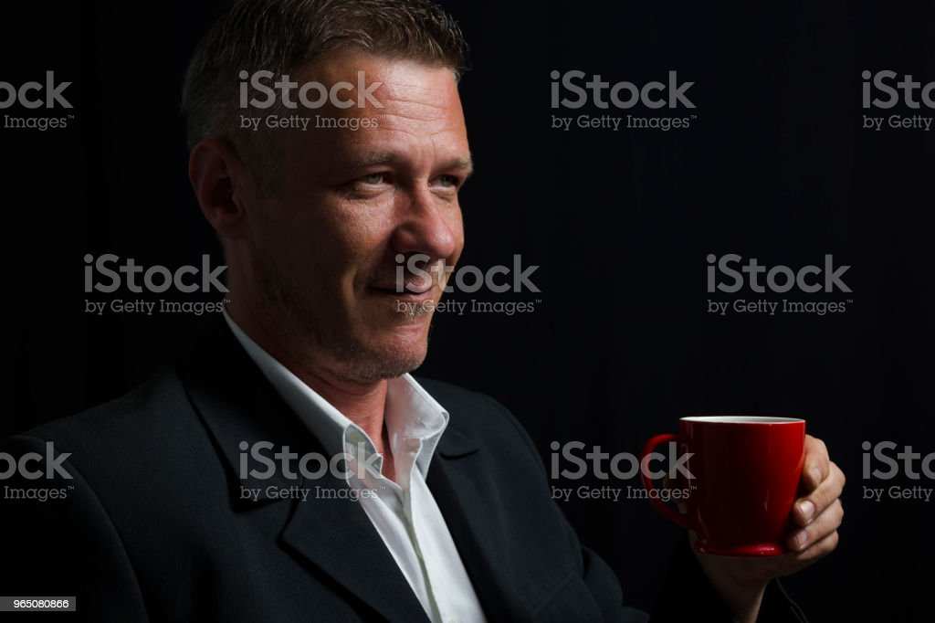 Satisfied adult man in black suit holding coffee cup in his hand in front of black curtain zbiór zdjęć royalty-free