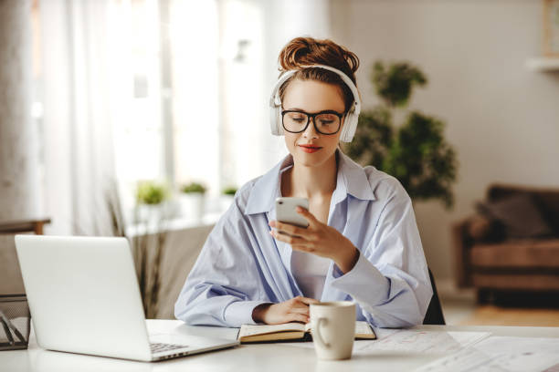 satisfied adult woman with coffee using smartphone while working at laptop in light living room - remote work imagens e fotografias de stock