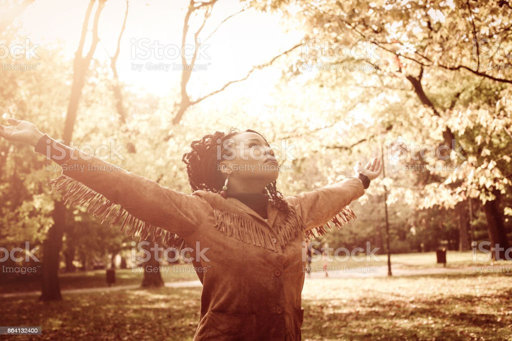 Satisfied African American girl with open arms dancing on meadow and looking in sky. royalty-free stock photo