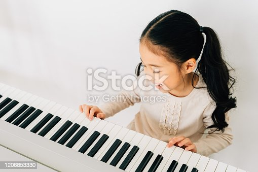 From above of happy smiling cute Asian girl playing piano enjoying time practicing music at home