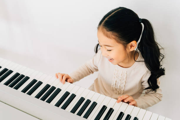 Satisfied Asian kid playing piano at home stock photo