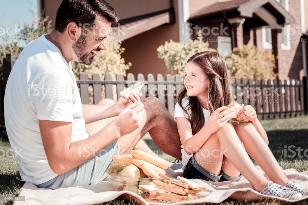 Satisfied attentive father eating a sandwich looking at his daughter. stock photo