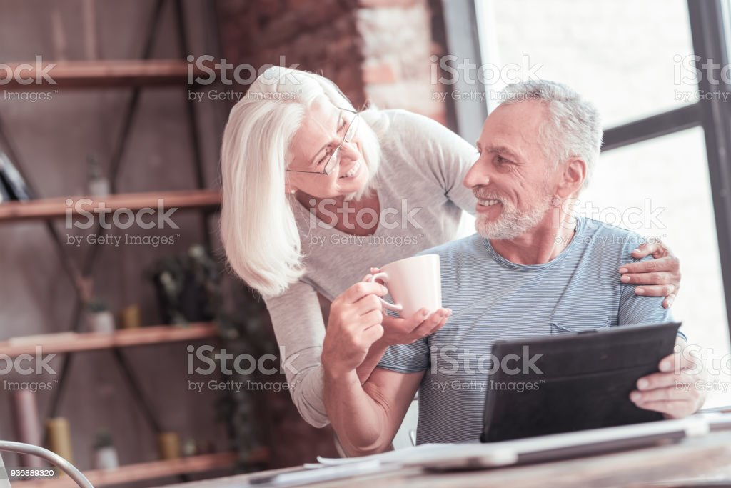 Satisfied bespectacled woman smiling and bringing a cup stock photo