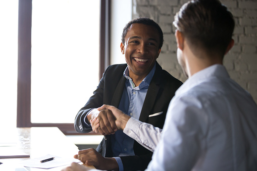 istock Satisfied black client shaking hands thanking manager for good deal 1085713922