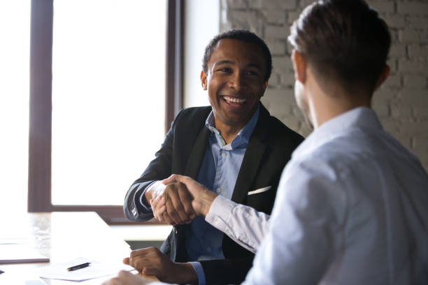 Satisfied black client shaking hands thanking manager for good deal Happy satisfied black client shaking hands thanking manager for good financial deal, african american businessman handshaking partner after successful business negotiations, hiring, buying services seller stock pictures, royalty-free photos & images