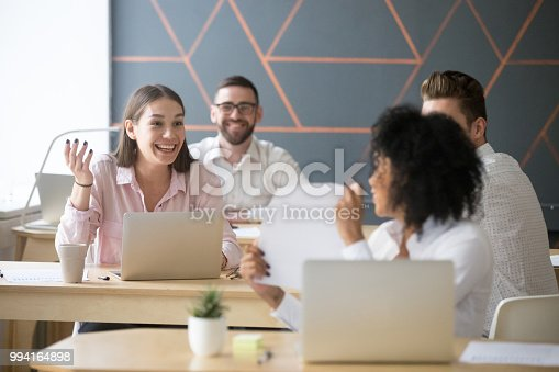 Excited colleagues cannot believe good report results or financial breakthrough on market, black female worker showing statistics to coworkers, praising high achievements or promotion. Reward concept
