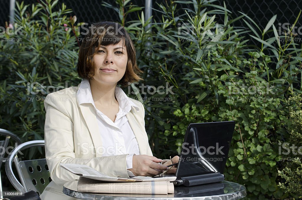 Satisfied Business woman sitting down with her personal computer stock photo
