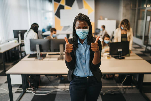 Satisfied business woman with protective face mask in modern office showing thumbs up stock photo