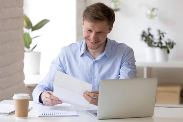 Satisfied businessman sitting at the desk reading letter picture id1131900944?b=1&k=6&m=1131900944&s=612x612&w=0&h= bhbwai2lgzpnonhz gudfmru kvuwd8ibhzs mq5t4=