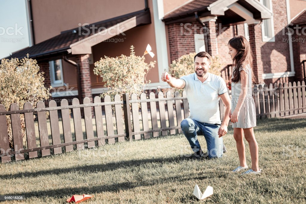 Satisfied caring father throwing the paper plane and smiling. stock photo