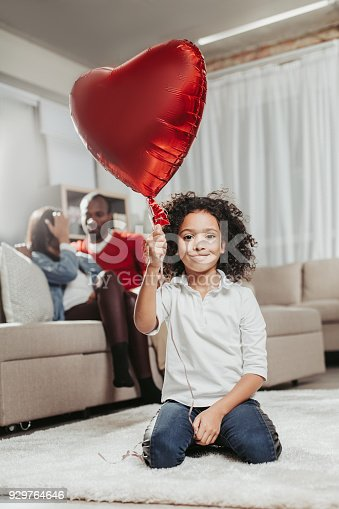Portrait of pleased daughter resting on tapis in living room and holding up heart balloon. Parents sitting on couch behind. Focus on girl
