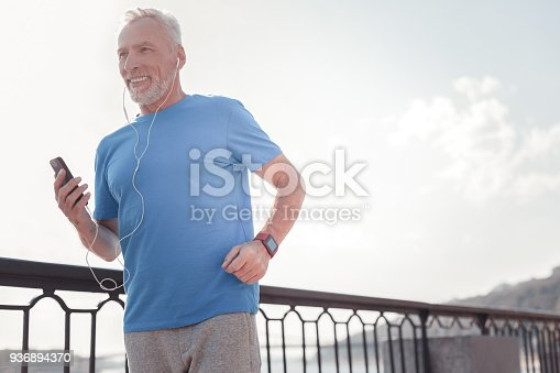 istock Satisfied confident man holding the smartphone and running 936894370