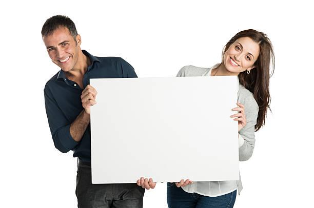 satisfied couple holding a placard - mid volwassen koppel stockfoto's en -beelden