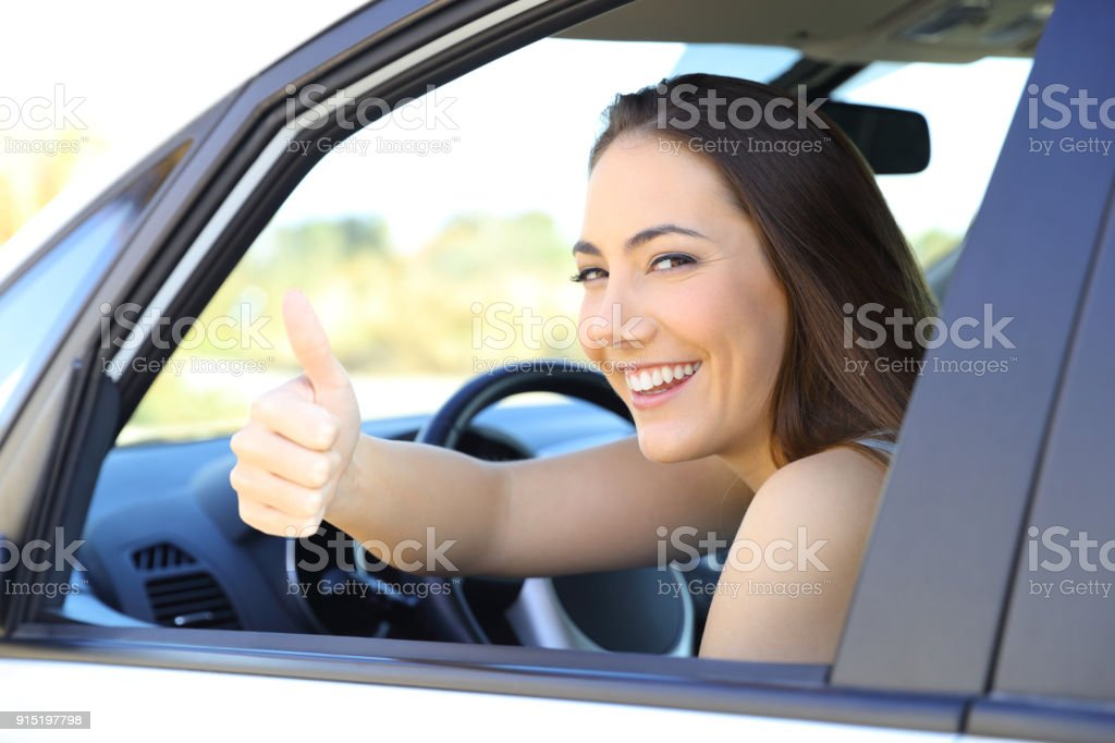 Satisfied driver with thumbs up in a car stock photo