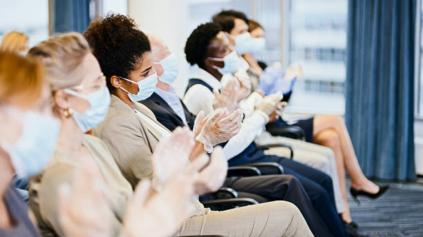 Satisfied entrepreneurs in protective masks applauding at conference. New normal stock photo