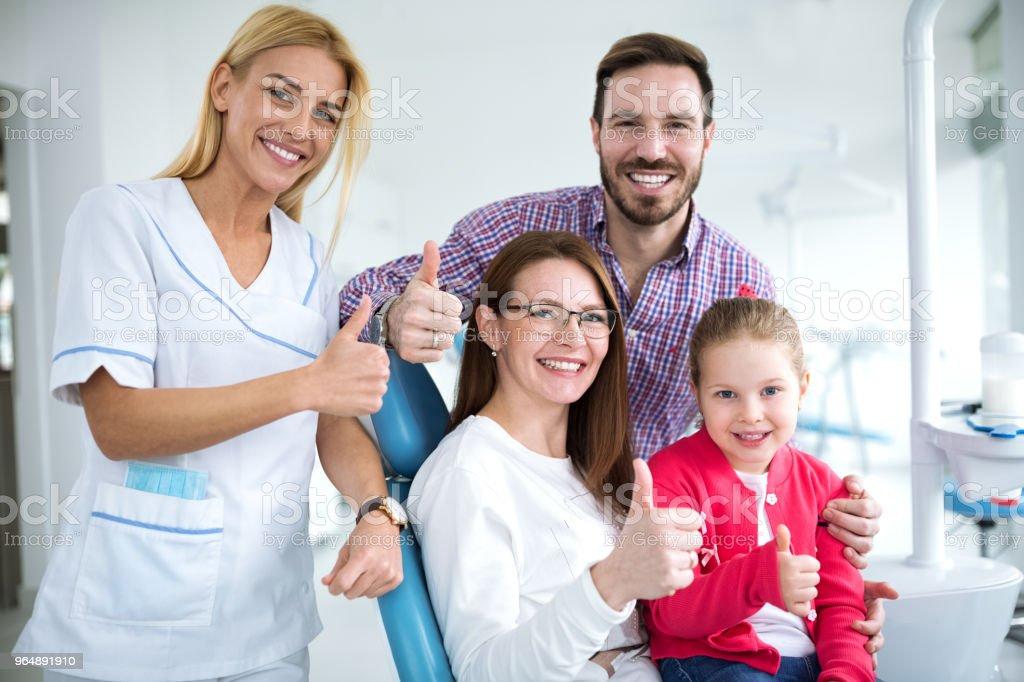 滿意的家庭與微笑的年輕女牙醫 - 免版稅一起圖庫照片