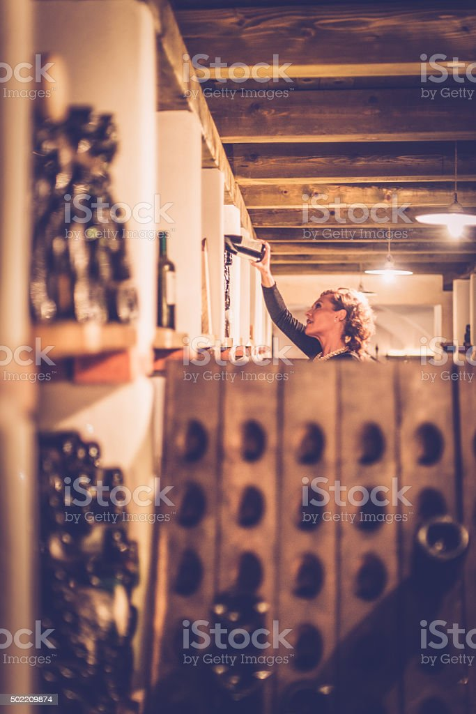 Satisfied Female Vintner Checking Wine Bottles, Cellar in Europe stock photo