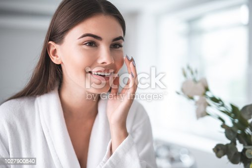 Portrait of pleased young lady touching cheek with hand. She putting cream on face skin indoor