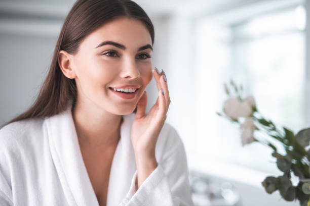 Satisfied girl doing face treatment in morning Portrait of pleased young lady touching cheek with hand. She putting cream on face skin indoor smooth stock pictures, royalty-free photos & images