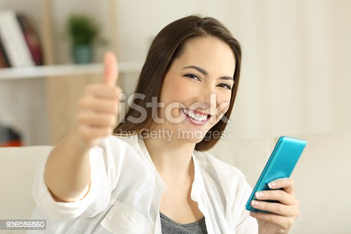 istock Satisfied girl holding smart phone with thumbs up 936586860