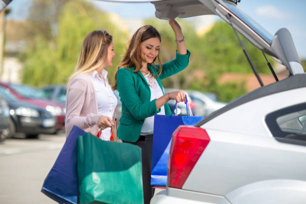 satisfied girls are put the bags in the car stock photo