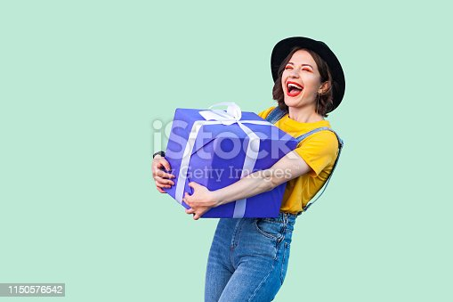 istock Satisfied happy beautiful young girl in hipster wear in denim overalls and black hat standing and holding big heavy gift box with toothy smile and laughing, open mouth. 1150576542
