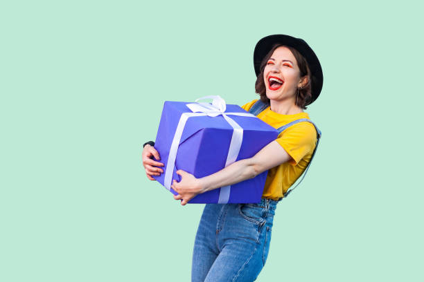 satisfied happy beautiful young girl in hipster wear in denim overalls and black hat standing and holding big heavy gift box with toothy smile and laughing, open mouth. - smile woman open mouth foto e immagini stock