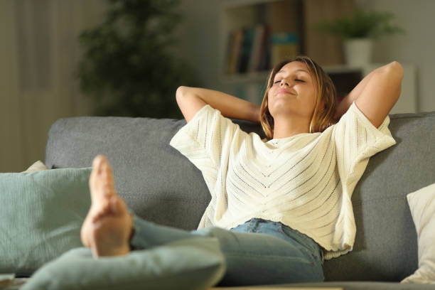 Satisfied homeowner resting on a couch Satisfied homeowner resting on a couch smooth stock pictures, royalty-free photos & images