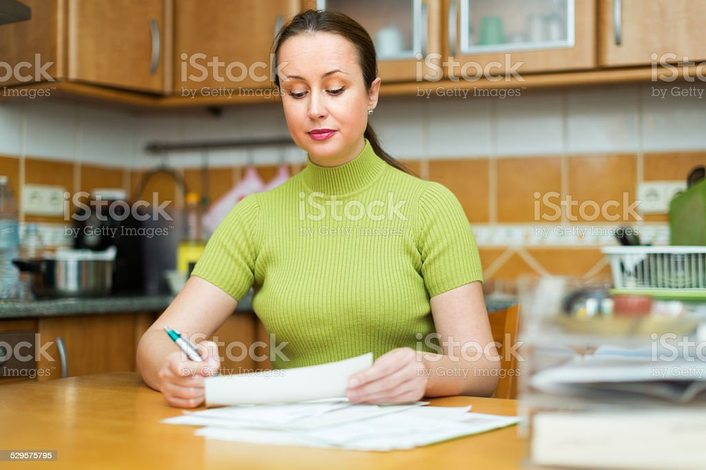 Satisfied housewife looking through bills stock photo
