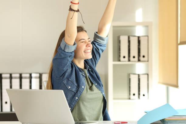satisfied intern raising arms at office - buona notizia foto e immagini stock