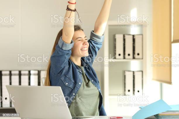 Satisfied Intern Raising Arms At Office Stock Photo - Download Image Now