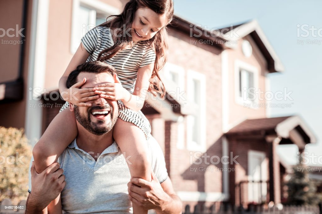 Satisfied little girl spending time with father and smiling. stock photo