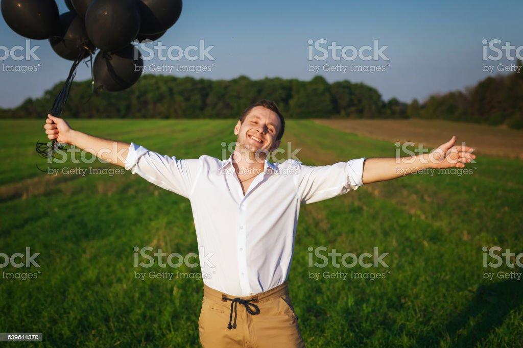 satisfied man holding black balloons stock photo