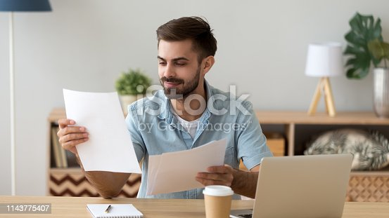 istock Satisfied man reading paper documents, working with laptop 1143775407