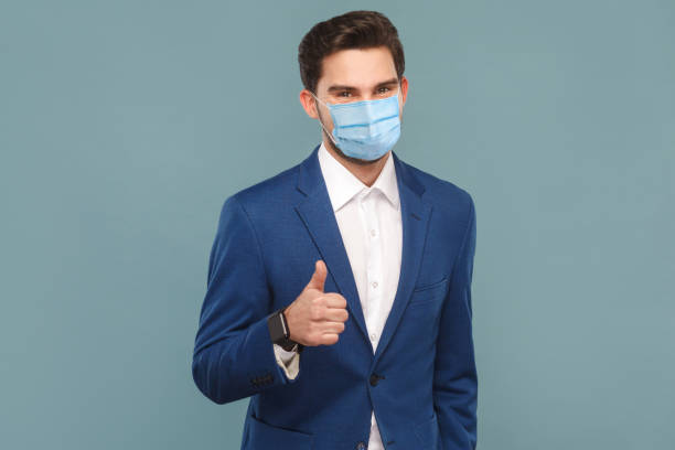 Satisfied man with surgical medical mask showing like sign thumbs up at camera. stock photo
