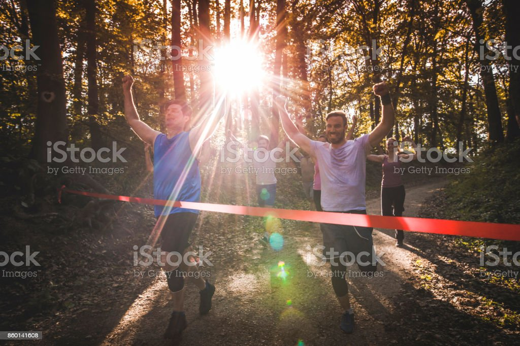 Satisfied marathon runners successfully finishing the race through the forest. stock photo