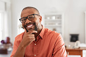 Cheerful black mature man wearing spectacles looking at camera. African businessman with hand on chin smiling while sitting at home. Happy man with eyeglasses enjoying new project.