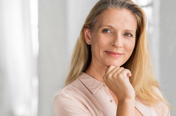 Satisfied mature woman Portrait of a senior woman thinking with hand on chin and looking away. Mature smiling woman feeling happy. Thoughtful retired woman planning her future. Vision concept. nude women pics stock pictures, royalty-free photos & images