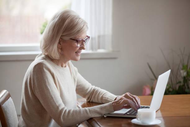 zufrieden reife frau nachricht mit notebook am tisch sitzen - brille bestellen stock-fotos und bilder