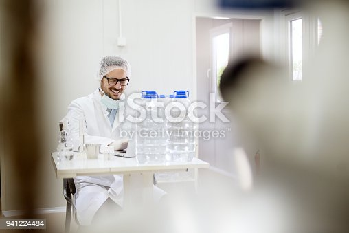 istock Satisfied motivated smiling scientist man working on a laptop at laboratory desk with bottles of water and flasks in front. 941224484