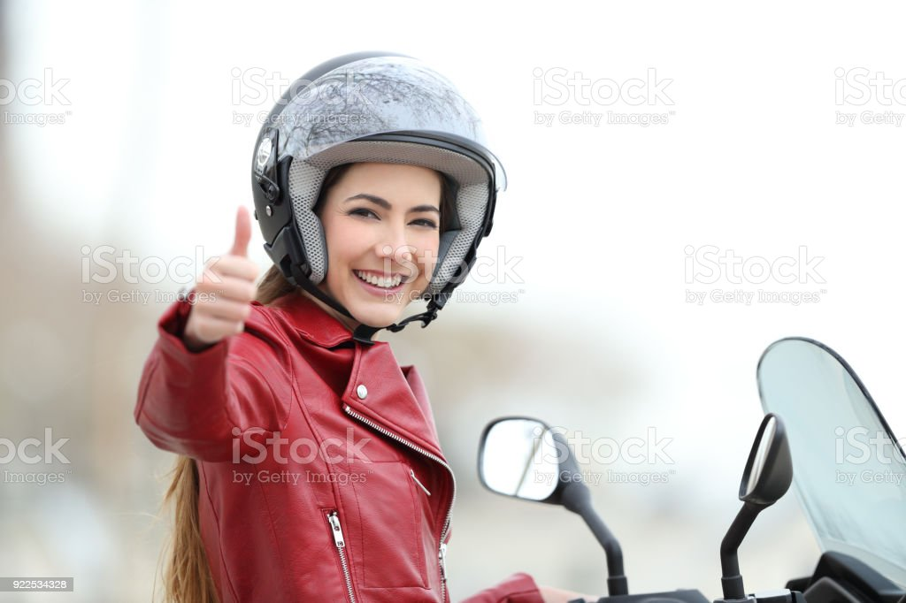 Satisfied motorbiker gesturing thumbs up stock photo