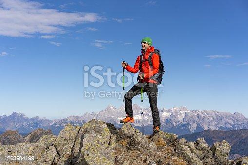 mature man hiker with hiking poles standing alone high up in the mountains on cold sunny autumn day, place for text
