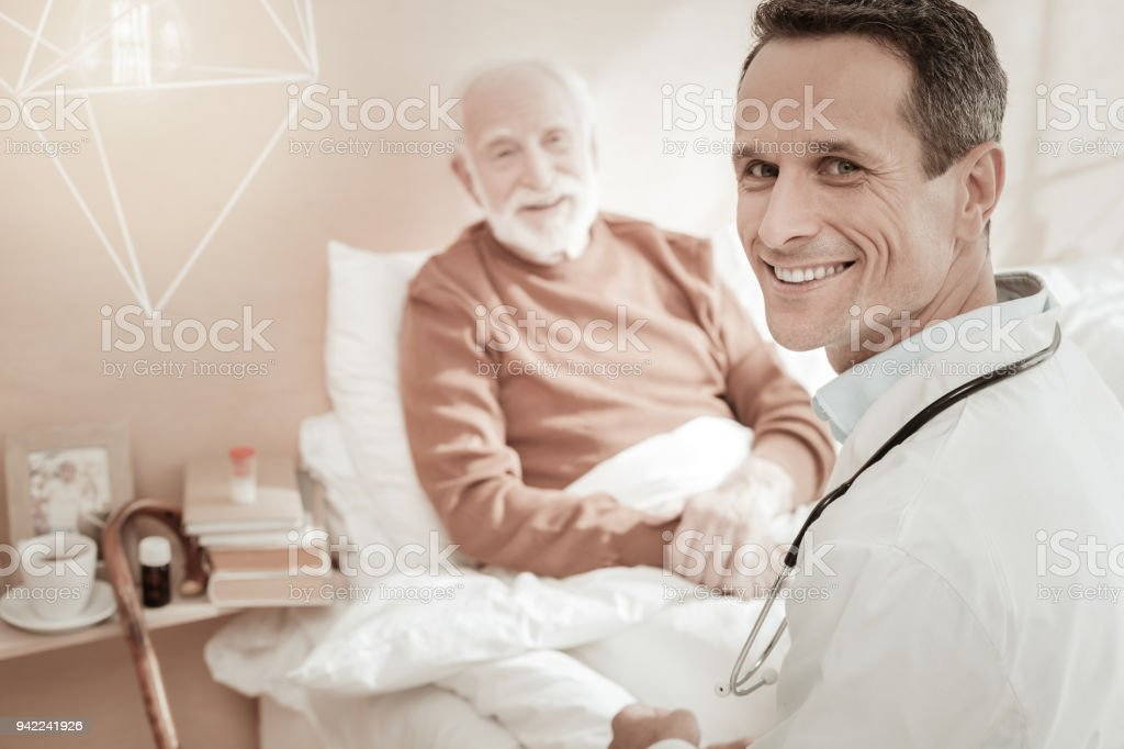 Satisfied qualified doctor smiling turning head. stock photo